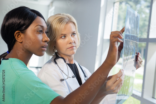 Female nurse and doctor looking at xrays