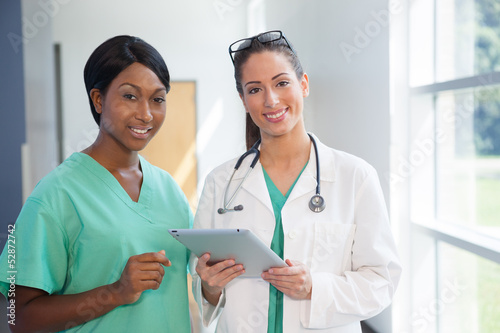 Female nurse and doctor with tablet computer