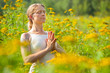 woman practicing yoga in meadow of yellow flowers