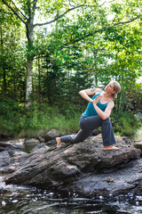 woman practicing yoga on rocks beside stream