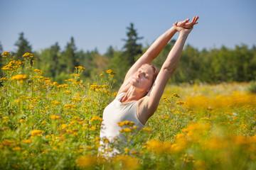 woman stretching in ragweed flowers