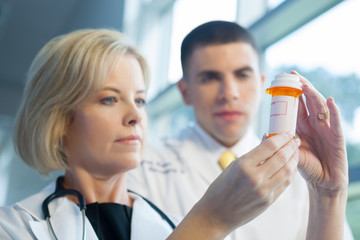 Doctors looking at prescription bottle