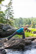 woman practicing yoga on rocks beside stream