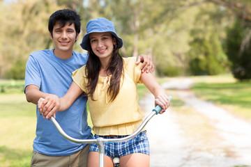 Young man and woman posing on bike