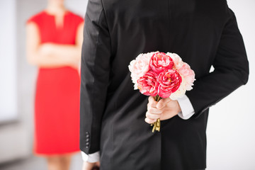 man hiding bouquet of flowers