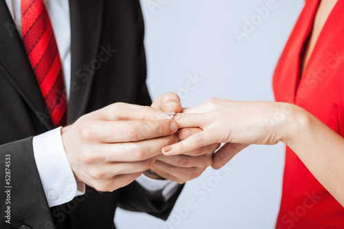 man putting  wedding ring on woman hand