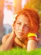 Redhead girl on green grass