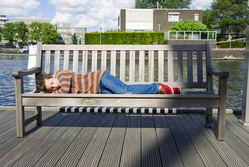 relaxed boy sleeping on the bench