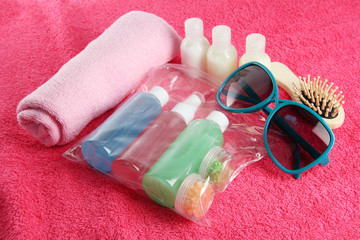 Hotel cosmetics kit on pink towel