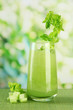 Glass of celery juice, on bamboo mat, on green background