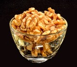 A glass bowl of walnuts on a black background.