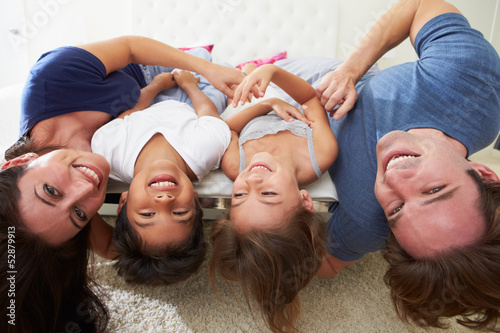 Family Lying Upside Down On Bed In Pajamas Together