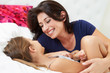 Mother And Daughter Lying In Bed Together