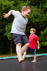 Children playing while jumping on trampoline outdoors on spring