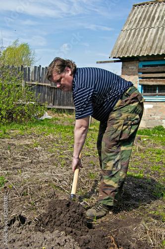 Мужчина вскапывает грядки весной