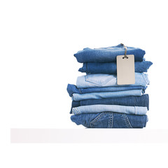 Pile of blue jeans with tag label on white shelf in shop.