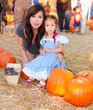 Beautiful Asian Mother and Daughter at a Halloween Pumpkin Patch