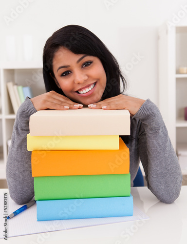 Young Woman Smiling On Stack Of Books