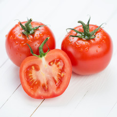 Close-up of two red ripe tomatoes and their segment