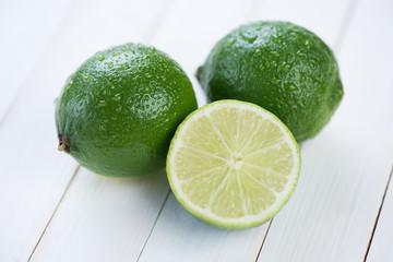 Two ripe limes and their segment, horizontal shot