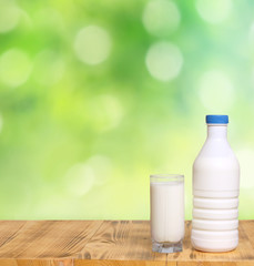Bottle of fresh milk and glass on a wooden table