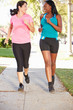 Two Female Runners Exercising On Suburban Street