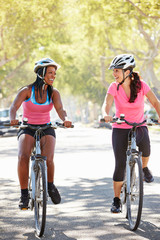 Two Women Cycling On Suburban Street