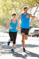 Woman Running Along Street With Personal Trainer
