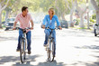Couple Cycling On Suburban Street
