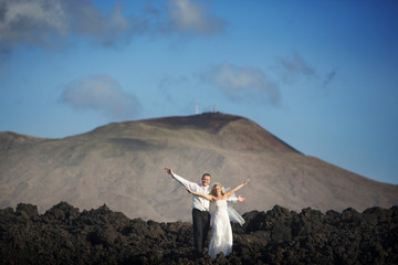 The bride and groom open arms to volcanic landscape background.