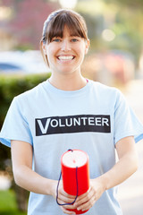 Portrait Of Charity Volunteer On Street With Collection Tin