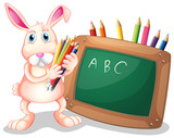 A bunny with coloring pens beside a blackboard