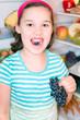 Mädchen nascht Weintrauben aus dem Küchlschrank