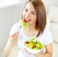 Teenager girl eating salad