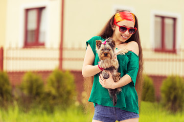 smiling girl with dog yorkie terrier on hands