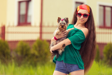 girl in sunglasses with dog yorkie on hands