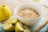 Oat flakes in bowl with apples and milk