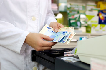 Money euros hold by pharmacist at counter