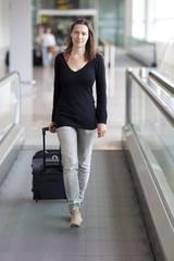 Frau rollt Koffer am Flughafen