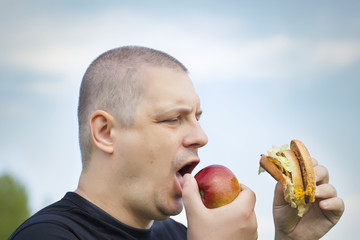 Man with burger and apple in the hands