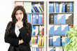 Young thinking business woman posing on office background