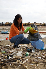 Young social worker cleaning dirty beach