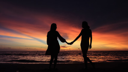 silhouette of two girls holding hands together on beach