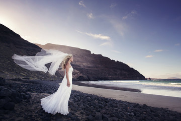 A bride standing in the ocean, the veil fluttering in the wind.
