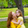 Mother kissing her blond daughter in green park