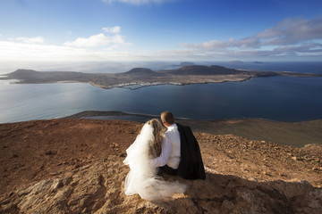 Bride and groom sitting on a volcanic landscape background.