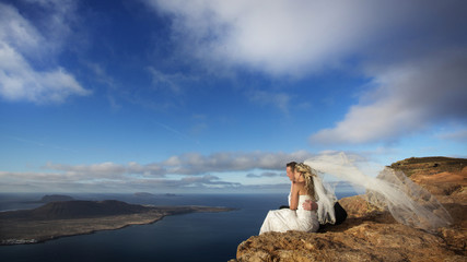 Bride and groom sitting on ocean shore, volcanic landscape.