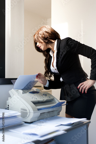 Young pretty business woman sending fax on office background