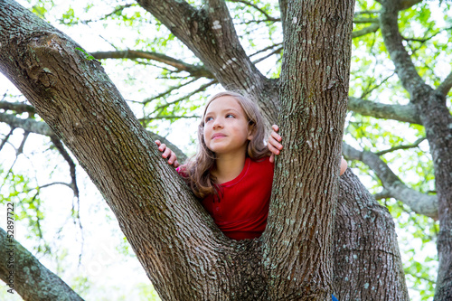 children kid girl playing climbing to a tree in a park