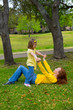 Daughter and mother playing lying on park lawn